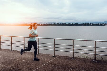 Beautiful woman running on the street with a view of the river in the morning. Stock Photo