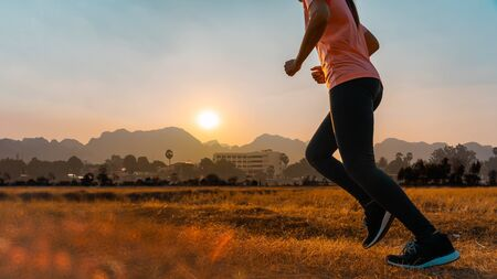 Asian woman enjoys running outside with beautiful summer evening in the countryside. Stock Photo