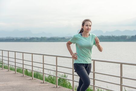 Beautiful woman running on the street with a view of the river in the morning. Reklamní fotografie