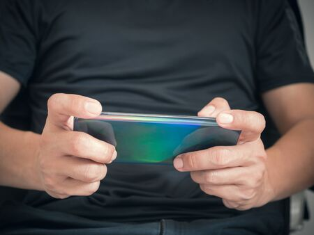 Man playing game on smartphone.