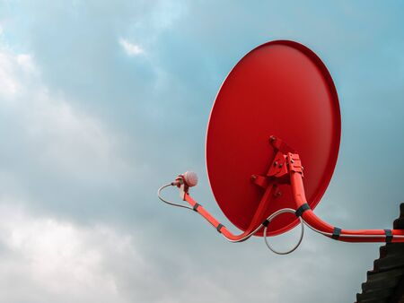Red satellite dish on house roof with sky background. Reklamní fotografie