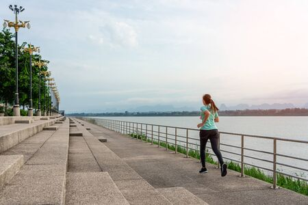 Young woman running on the street with a view of the river in the morning.