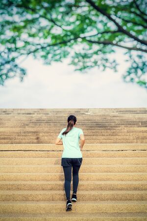 Young woman running up on stairs in the park. Reklamní fotografie