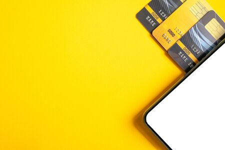 Credit cards and smartphone on yellow background. Stock Photo