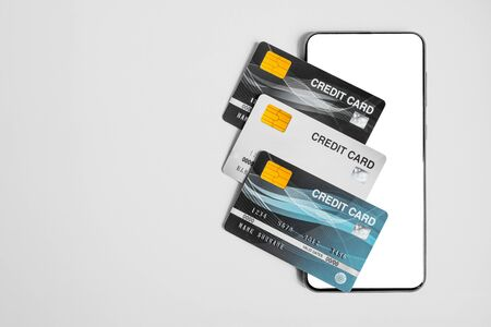 Credit cards and blank smartphone on gray background.