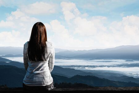 Young traveler woman is sitting looking at the view of mountains natural background. Reklamní fotografie