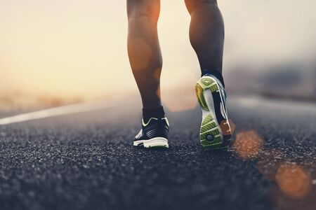 close up sport shoes of a runner on road for fitness healthy lifestyle. Reklamní fotografie
