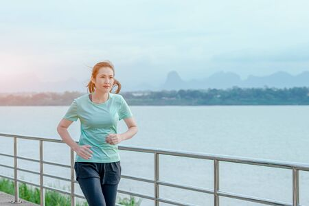 Beautiful woman running on the street with a view of the river in the morning. 版權商用圖片