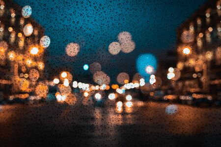 Raindrops on window of car with the rainy season in blur night city background.