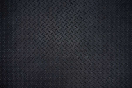 Close-up photos of Black metal floor plate texture details background. Dark wall and copy space.