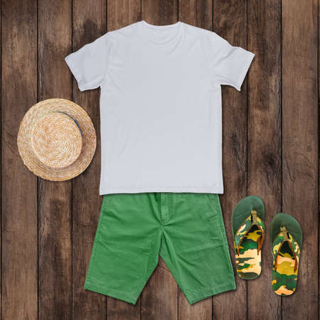 Top view of White t-shirt with green shorts, sandals, hat placed on the wooden floor.