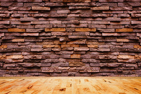 Empty wood floor texture with decorative stone wall background. Stock Photo