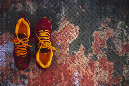 Close-up Sport shoes on old metal floor plate texture background.