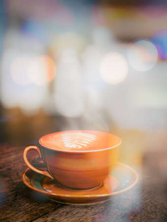 A view through the window glass of a hot coffee cup on an old wooden table in a cafe.