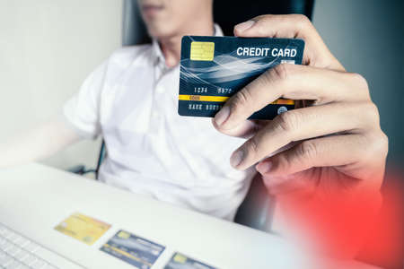 Man paying with credit card on computer at home.
