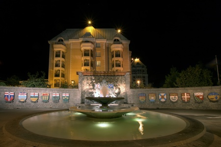 confederation: Confederation Garden Court Fountain in Victoria BC Canada with Code of Arms at Night Stock Photo