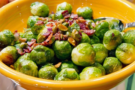 Thanksgiving Day Dinner Brussels Sprouts Dish with Bacon Bits and Pistachios Nuts Closeup