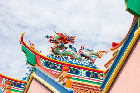 Colorful Chinese Dragon Sculpture on Temple Roof Top Against Blue Sky photo