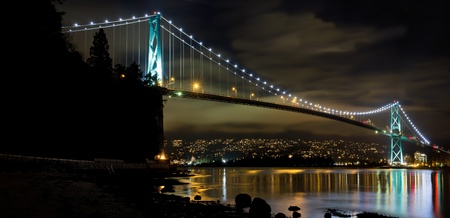 bc: Lions Gate Bridge over Burrard Inlet in Vancouver BC Canada at Night Panorama Stock Photo