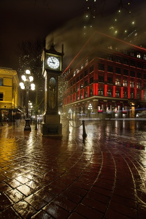 Gastown Steam Clock in Vancouver BC Canada on a Rainy Night with Historic Red Building Banco de Imagens