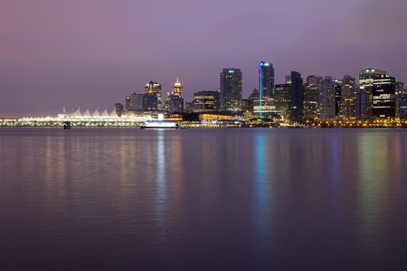 Vancouver BC City Skyline and Stanley Park along Burrard Inlet at Break of Dawn Stock Photo