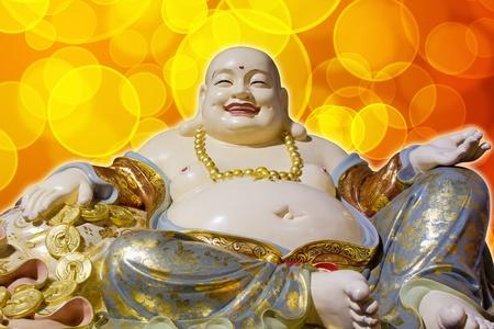 smiling buddha: Big Belly Maitreya Cloth Bag Monk Happy Buddha Statue Isolated on Blurred Background
