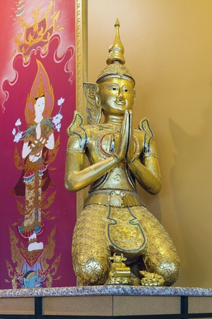 Thai Teppanom Angel Statue and Goddess Painting in Background photo