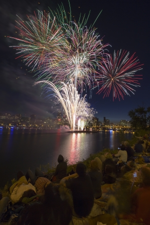 People Watching Fireworks Display Along the Banks of Willamette River in Portland Oregon Vertical photo