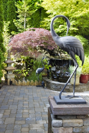 Bronze Cranes Sculpture in Japanese Inspired Zen Garden with Pagoda and Waterfall photo