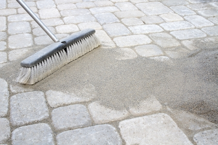 Broom Sweeping Locking Sand Into Backyard Patio Pavers photo