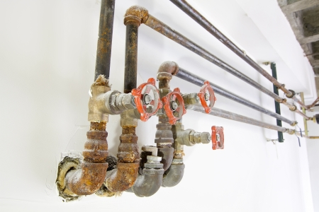Old Heating Cooling Water Plumbing Pipes with Valves on White Wall