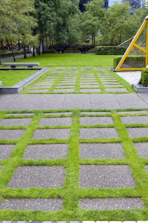 hardscape: Grass Growing Between Concrete Pavers in Public Parks Landscaping Stock Photo
