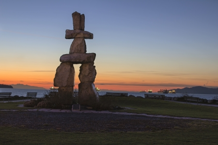 inlet bay: Inukshuk Stone Sculpture on Sunset Beach Alond English Bay in Vancouver BC Canada during Sunset