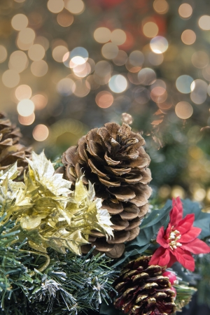 festive pine cones: Christmas Decoration Garland with Poinsettia Pine Cones and Colorful Blurred Bokeh Lights Background Stock Photo