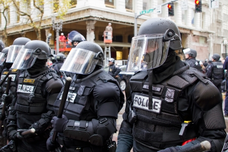 police badge: PORTLAND, OREGON - NOV 17, 2011 - Police in Riot Gear in Downtown Portland, Oregon during a Occupy Portland protest on the first anniversary of Occupy Wall Street November 17, 2011
