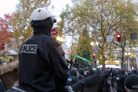 occupy wall street: PORTLAND, OREGON - NOV 17, 2011 -  Mounted Police Watching over protestors in Downtown Portland, Oregon during a Occupy Portland protest on the first anniversary of Occupy Wall Street November 17, 2011