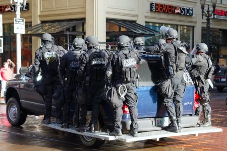 bullet proof: PORTLAND, OREGON - NOV 17: Oregon State Trooper in Riot Gear on Vehicle in Downtown Portland, Oregon during a Occupy Portland protest on the first anniversary of Occupy Wall Street November 17, 2011 Editorial