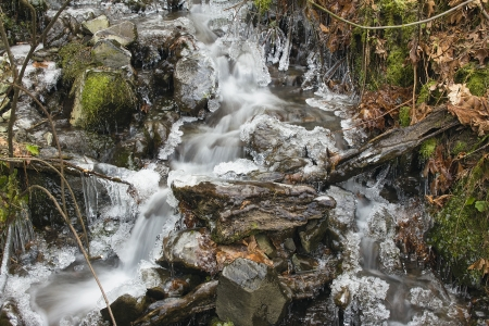 Small Stream with Water Flowing and Icicles Formation in Winter photo