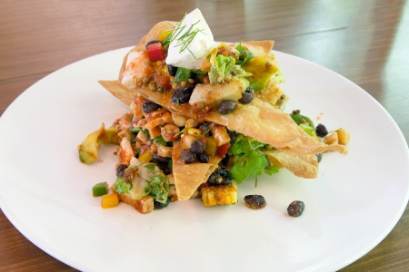 Mexican Chicken Salad with crispy tortilla avocado black beans spiced corn sour cream and salsa photo