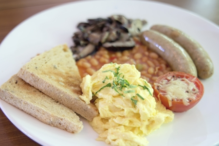 Scrambled Eggs Sausages with Bread Toast Baked Beans Sauteed Mushrooms and Tomato with Melted Cheese Breakfast photo