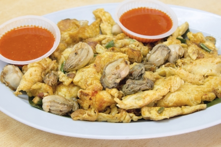 chien: Southeasat Asian Fried Baby Oyster Omelette Oh Chien with Chili Sauce Closeup