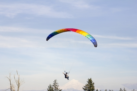 parasailing: Paragliding Over Mount Hood with Rainbow Colored Parachute Stock Photo