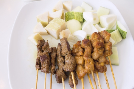 Mutton and Chicken Satay with Chopped Cucumbers Onions and Ketupat Rice Cake Vertical
