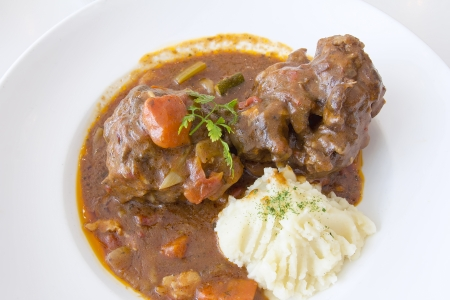 mashed: Ox Tail Beef Stew with Mashed Potatoes Dish Closeup Stock Photo