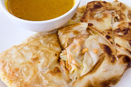 Indian Roti Prata with Chicken Meat and Curry Sauce Closeup