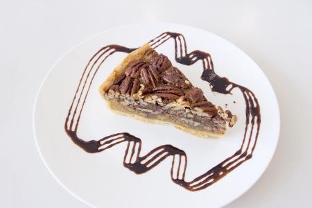 pecan pie: Nueces Pecan Pie con la rebanada con la llovizna del chocolate oscuro en la placa blanca