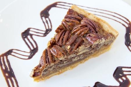 pecan pie: Nueces Pecan Pie con la rebanada con llovizna del chocolate oscuro en Primer Plato Blanco