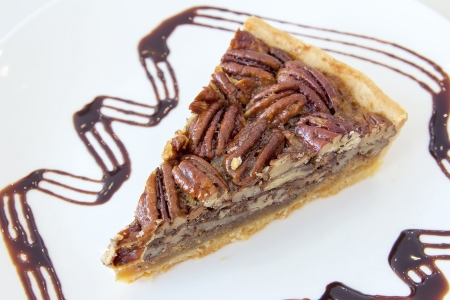 pecan: Pecan Nuts Pie with Slice with Dark Chocolate Drizzle on White Plate Closeup Stock Photo