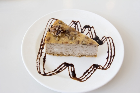 Walnut Cheesecake Slice with Dark Chocolate Drizzle on White Plate photo
