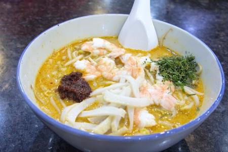 Singapore Curry Laska with Prawns Fishcake and Sambal Chili Paste Macro photo